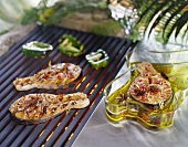 Two salmon steaks on barbecue, on with marinade beside it