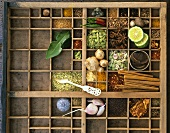 Assorted spices and kaffir limes in typesetter's box