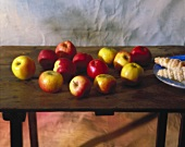 Various types of apples and baked goods on a wooden table