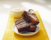 Three pieces of chestnut cake; cream in small bowl