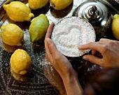 Finger malen ein Herz in ein Schälchen Salz, daneben Zitronen