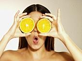 Frau hält zwei Orangenscheiben vor die Augen