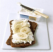 Wholemeal bread topped with soft cheese and banana slices
