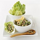 Bulgur wheat salad (tabbouleh) in small bowl & on lettuce leaf