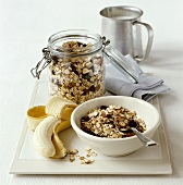 Bowl of muesli with banana and milk jug