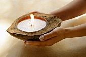 Hands holding half a coconut with a scented candle