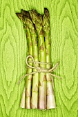A bundle of green asparagus against green background