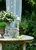 Tisch gedeckt mit Blumen, Töpfen und Äpfeln
