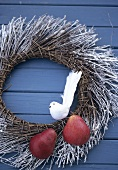 Wreath with pears & an artificial bird on blue wooden wall