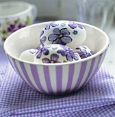 Easter eggs with painted flowers in a bowl