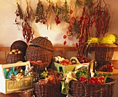 Baskets of vegetables, preserves; herbs etc. on wall