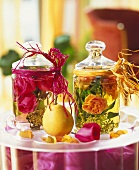 Glass containers with rose water and flowers