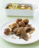Lamb with garlic, roast potatoes and vegetable gratin