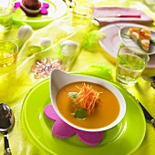 Carrot and lemon soup on table laid for Easter