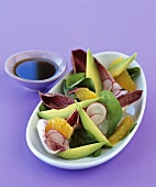Avocado salad with radish slices and orange segments