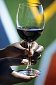 Hand hält ein Glas Rotwein vor südafrikanischer Fahne
