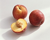 Peach, variety 'Flavor Crest', whole and halved