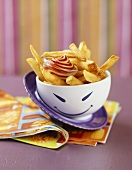 A bowl of chips with ketchup & mayonnaise for kid's party