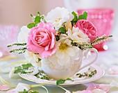 weiße und rosa Rosen und Heide in einer Tasse