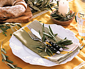 Laid table decorated with olive leaves