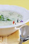 Miniature cleaning ladies scrubbing edge of plate of leek soup