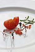 Fussballfiguren trainieren auf Teller mit Tomatenwürfeln