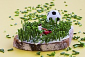 Miniature footballer mowing  bread & butter with chives