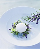 Lighted floating candle with ring of herbs on a plate