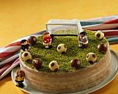 Fussballtorte dekoriert mit Fussballfiguren auf Pistazien