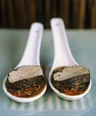 Pork fillet in pepper sauce on two spoons (Vietnam)