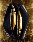 Two smoked mackerel on golden background