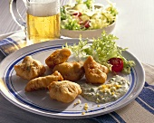Deep-fried fish in beer batter with salad and beer