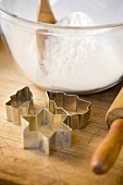 A bowl of flour with biscuit cutters