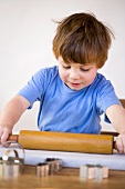 Boy rolling out biscuit dough