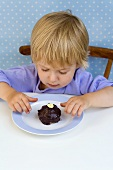 Small boy looking at a small chocolate cake