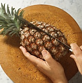 Cutting through a whole pineapple on a wooden plate