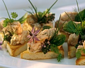 Slices of toast with ham mousse, herbs and flowers