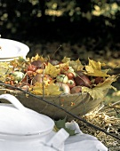 A Wooden Bowl with Apples Outside; Autumn Leaves