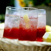 Several glasses of Campari with ice & lemon on wicker tray