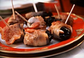 Bacon rolls stuffed with plums & almonds on skewers