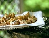 Several filled crepe rolls on wooden cocktail sticks