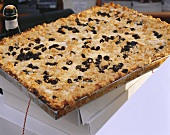 Cheese crumble cake with raisins on baking tray on boxes