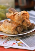 Sausage rolls on table with playing cards