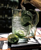 Pouring Water into Glass from Pitcher; Lime Peels