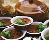 Lots of plates of chili con carne with coriander