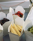 Olives, corncobs and gherkins in boxes