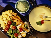 Cheese fondue with parsley & avocado dip, vegetables, bread