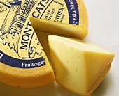 French Trappist cheese with a piece cut out & a piece of cheese