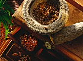 Sichuan peppercorns, whole and ground in stone mortar
