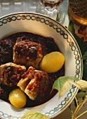 Pieces of eel in red wine sauce with prunes & potatoes